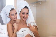 Ståenden för Skincare rengöringhud av kvinnor med handduken på huvudet som trycker på deras framsidor, reflekterade i spegel Arkivfoton