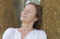 Mogna den stängda kvinnan som kopplas av, synar utomhus- Arkivfoto