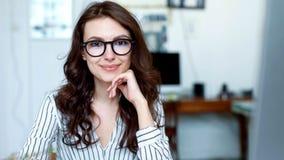 Ståenden sköt av den attraktiva kvinnan som ser kameran och ler, medan arbeta i det stads- kontoret close upp stock video