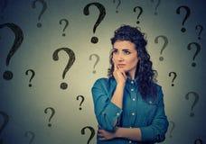 Ståenden som den förbryllade förvirrade kvinnan behöver en lösning, har många frågor arkivbilder