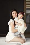Ståenden spelar en moder med en liten dotter Arkivfoto