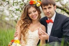 Ståendenygifta personer i den frodiga vårträdgården Royaltyfri Fotografi