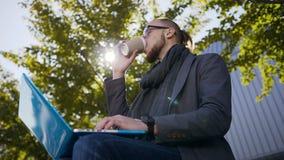 Ståendeskott av den stiliga Caucasian unga mannen med ett skägg som sitter på bänken med bärbara datorn Pojke, i att gå för expon stock video
