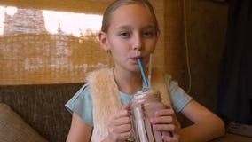 Ståendetonåringflicka som dricker upp milkshakecoctailen på tabellen i kaféslut stock video