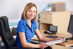 StåendeUK-doktor som sitter på skrivbordet Arkivfoto