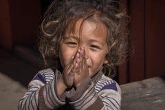 Ståendeung flicka med vikta händer i gata, Nepal close upp Arkivbild