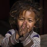 Ståendeung flicka med vikta händer i gata, Nepal close upp Royaltyfri Foto