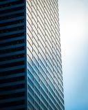 Stål- och exponeringsglasbyggnad och molnig himmel Arkivfoto