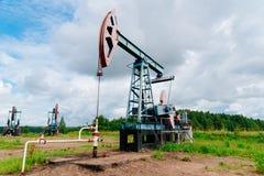 Stålar för olje- pump i fältet i Ryssland under molniga himlar Arkivfoto