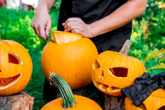 Stålar-nolla-lykta med man& x27; s-handen klipper ett lock från pumpa på bakgrund halloween Garnering för parti Fotografering för Bildbyråer