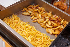 Stålbehållaren med grillade potatiskilar, fransman steker Arkivbild