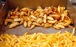 Stålbehållaren med grillade potatiskilar, fransman steker Arkivbilder