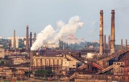 Stålfabrik med fabriksskorsten på solnedgången Royaltyfri Bild