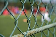 Stålingreppsstaket på sportfältet Mot fotbollen för bakgrundsfolklek fotografering för bildbyråer