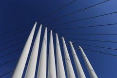Stålkolonner och kablar av den moderna bron som upp ser blå himmel royaltyfri bild