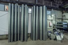 Stålrör och andra delar för konstruktion av kanaler av industriell luft betingar systemet i lagret royaltyfri bild
