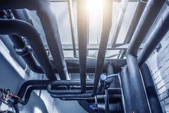 Stålrörledningar och ventiler under taket eller celling som abstrakt industriell bakgrund royaltyfria foton