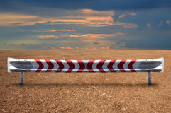 Stålsätta hårt guardrailen smutsar på land med den dramatiska färgrika skyen Royaltyfria Foton
