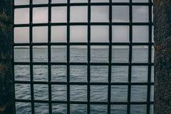 Stålsätta ingreppsrasterfönstret i en slott som ut ser på havet royaltyfri bild