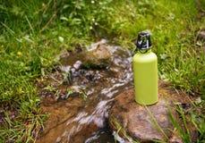 Stålsätta termoset med vatten på stenen nära bergfloden Royaltyfria Foton