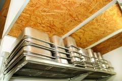 Stålsätta tjänste- behållare för glass som packas på buntar på hyllan Industriell förberedelse av krämig glass Arkivfoto