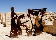 Stålstatyer illustrerar kommers på ett forntida shoppar på Avdat Arkivbild