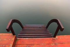 Stålvattentrappa, en trappa som så leder till vattnet på en fartyglandning med naturlig lugna vattenyttersidabakgrund Vila royaltyfria foton