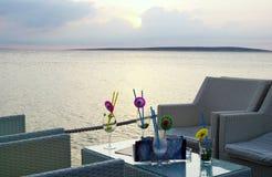 Stång för havssiktsvardagsrum på solnedgången med tomma exponeringsglas på tabellen royaltyfri fotografi