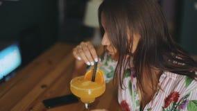 Stång för sammanträde för attraktiv telefon för kvinna som smart mobil dricker le för sikt för sida för stående för sommarcoctail arkivfilmer