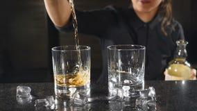 Stång i nattklubb Hällande whisky för kvinnlig bartender ut ur grej in i ett exponeringsglas i ultrarapid Oigenkännlig kvinnlig lager videofilmer