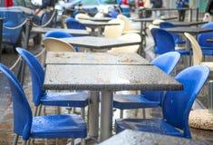 Stångtabeller och stolar under regnet Arkivbild