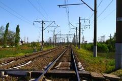 Stångvägen på landssida i sommar med mycket elektriska poler på den sid på bakgrund för blå himmel Arkivbild