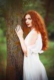 Står den bärande vita klänningen för den härliga rödhårig mankvinnan det near trädet Royaltyfria Foton