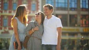 Står den bärande vita skjortan för den stiliga mannen på den gamla stadsfyrkanten med två nätta härliga flickor i innegrej arkivfilmer