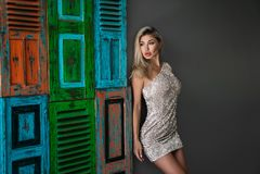 Står den iklädda skinande klänningen för den härliga blonda flickan på grå bakgrund med den kulöra fönsterskyddsgallret Den fanta Arkivfoto