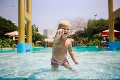 står den lilla blonda flickan för closeupen i pölvattenpunkter in mot Arkivbilder