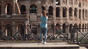 Står den turist- kvinnan för brunetten tillbaka till kameran i Rome, Italien som tar foto av Colosseumen med smartphonen långsam  lager videofilmer