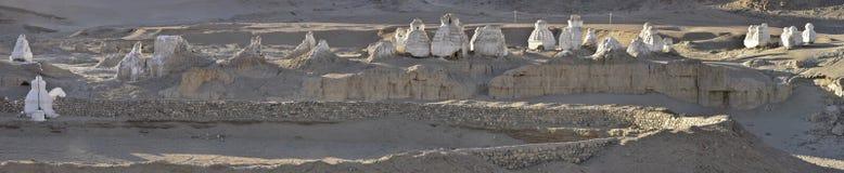 Står tibetana stupas för forntida vit sten på kanten av klippan som är upplyst vid strålarna av resningsolen, Ladakh, nordliga In Arkivbild