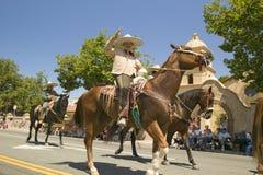 Ståta deltagare på hästrygg gör deras nedgång den huvudsakliga gatan under en fjärdedel av Juli att ståta i Ojai, CA Royaltyfri Bild