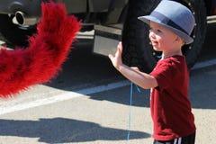 Ståta med dräkten av Elmo och barnet som smäller händer Arkivfoto