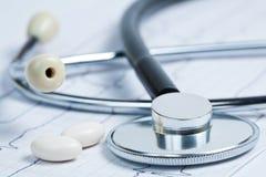 Stéthoscope avec des pillules sur l'électrocardiogramme Image libre de droits