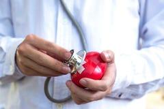 Stéthoscope avec le coeur dans des mains de docteur, Photographie stock