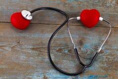 Stéthoscope avec le coeur rouge sur un fond en bois Photos libres de droits