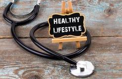 Stéthoscope avec le tableau noir avec le texte : mode de vie sain sur le bois photos libres de droits