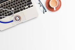 Stéthoscope bleu avec la tasse du café, des verres et de l'ordinateur portable Photo libre de droits