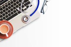Stéthoscope bleu avec la tasse du café, des verres et de l'ordinateur portable Photos libres de droits