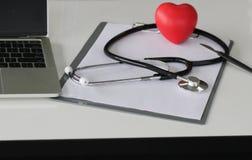 Stéthoscope, coeur, ordinateur et diagramme sur le fonctionnement de table du docto photographie stock