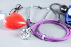 Stéthoscope, coeur rouge, verres et mètre de tension artérielle sur le fond blanc Foyer sélectif Photographie stock
