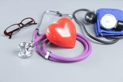 Stéthoscope, coeur rouge, verres et mètre de tension artérielle sur le fond blanc Foyer sélectif Image stock