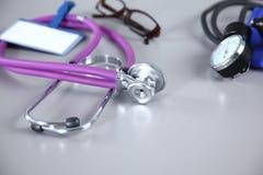 Stéthoscope, coeur rouge, verres et mètre de tension artérielle sur le fond blanc Foyer sélectif Photographie stock libre de droits
